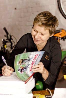 Magdalena Sadłecka podpisuje książkę Kolarstwo podstawy treningu