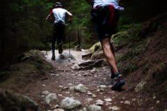 Trening wysokogórski z kijkami - zdjęcie pokazujące dwóch biegaczy z czego jeden pomaga sobie kijami