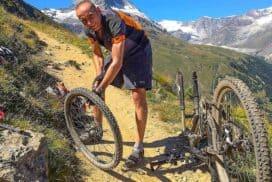 mężczyzna naprawiający rower na tle gór