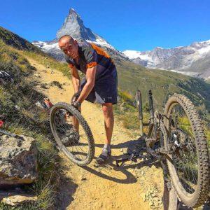 mężczyzna naprawiający rower natle gór