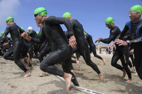 triathloniści biegnący do wody