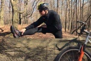 rozciąganie potreningu rowerowym - rowerzysta rozciąga się wplenerze