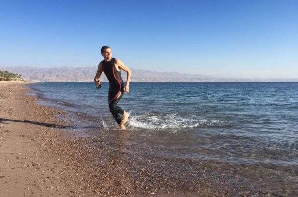 przejście z basenu na wody otwarte - mężczyzna wychodzi z moża po odbytym treningu pływackim