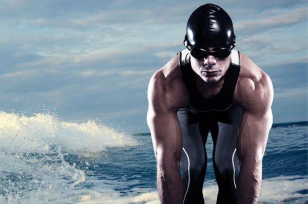 rola treningu siłowego w triathlonie - mężczyzna w kostiumie na tle morza