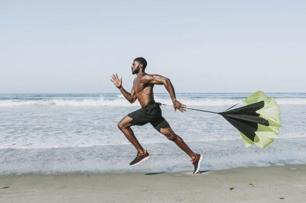 stan przepływu w sporcie - mężczyzna biegnie po plaży ze spadochronem treningowym