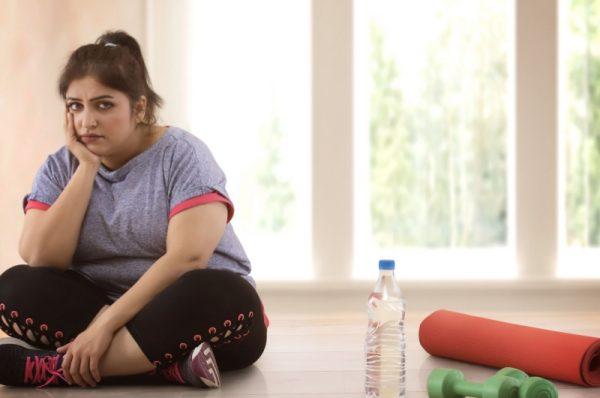 aktywność fizyczna a zdrowie - otyła dziewczyna siedzi na podłodze a obok niej leży zwinięta mata i hantle