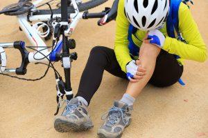 kontuzja kolarza - kolarz siedzi i obejmuje się za nogę