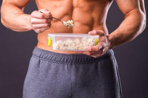 odżywianie sportowców - mężczyzna w stroju sportowym z posiłkiem w pudełku