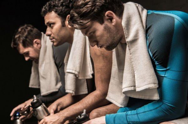 regeneracja po treningu trzech mężczyzn na ławce z ręcznikami na szyjach
