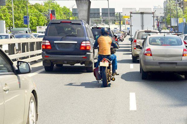 Jazda motocyklem po linii między samochodzami