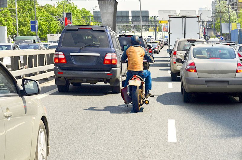 Jazda motocyklem polinii między samochodami