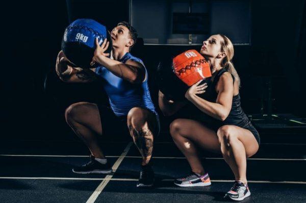 progresja w treningu siłowym - zdjęcie kobiety i mężczyzny na siłowni ćwiczących z różnej wielkości piłkami lekarskim