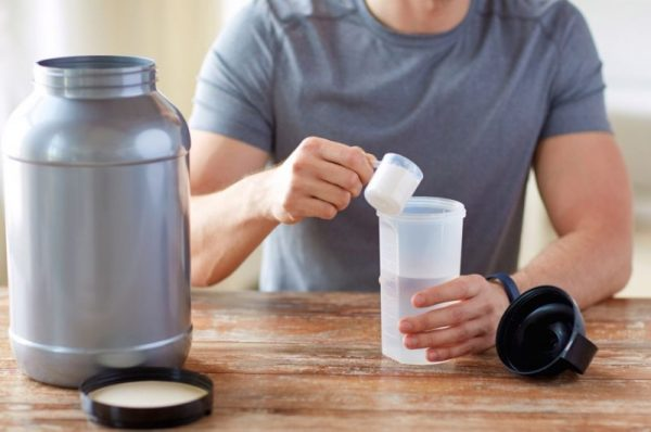 mity na temat żywienia sportowców - odzywki białkowe pomagają we wzroście mięśni. mężczyzna przygotowuje sobie koktajl białkowy